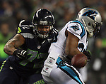 Seattle Seahawks defensive Michael Bennett (72) strips the ball from Carolina Panthers running back Jonathan Stewart (28)  in the NFC Western Division Playoffs at CenturyLink Field  on January 10, 2015 in Seattle, Washington. The Seahawks beat the Panthers 31-17. ©2015. Jim Bryant Photo. All Rights Reserved.