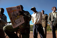 Kenyan men on the streets of Iten, Kenya read about Salina Kosgei's victory in the  2009 Boston marathon..