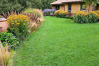 Small green grass lawn by California home with flower border garden