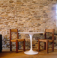 Old mixes effortlessly with new: a pair of 19th century French country chairs coupled with an iconic Saarinen 'tulip' table against a stone wall