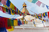 Prayer flags at  the white Stupa at Boudhanath in Nepal. Boudhanath is one of the holiest Buddhist sites in Kathmandu, Nepal. The Buddhist stupa of Boudhanath dominates the skyline. The ancient Stupa is one of the largest in the world. The Stupa is on the ancient trade route from Tibet which enters the Kathmandu Valley. Tibetan merchants have rested and offered prayers here for many centuries. When refugees entered Nepal from Tibet in the 1950s, many decided to live around Boudhanath. The Stupa is said to entomb the remains of Kassapa Buddha.
