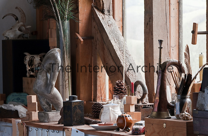A sculptured torso, an old tea caddy and antique post-horn are just some of the eclectic objects displayed in front of this window