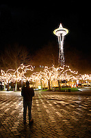 Nighttime scene of man standing on walkway in Seattle Center decorated with Christmas lights below Seattle Space Needle, Seattle Center, Seattle, Washington, USA