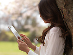 Young woman with iPad tablet computer in a park under a cherry tree
