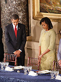 Washington, DC - January 20, 2009 -- This January 20, 2009 file photo shows United States President Barack Obama and first lady Michelle Obama as they pray before lunch at Statuary Hall in the U.S. Capitol  in Washington.  The color of Michelle Obama's Isabel Toledo ensemble appeared to shift and change all day Tuesday, leading some observers wondering what to call the shade.  .Credit: Lawrence Jackson - Pool via CNP