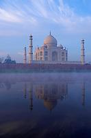 Sunrise and fog rising over the Yamuna River with the Taj Mahal, Agra India