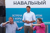 Moscow, Russia, 13/08/2013.<br /> Russian opposition blogger and political activist Alexei Navalny looks on as a member of the audience asks questions and another signals he is taking too long during a meeting outside a shopping mall as Navalny campaigned as a candidate for Moscow Mayor in elections scheduled for September 8th.