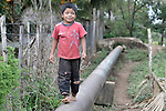 A Guatemalan boy walks along an oil pipeline that crosses the large section of the north of the Central American country.