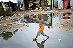 A boy navigates a flooded portion of a camp for internally displaced families located inside a United Nations base in Juba, South Sudan. The camp holds Nuer families who took refuge there in December 2013 after a political dispute within the country's ruling party quickly fractured the young nation along ethnic and tribal lines. More than 20,000 people are living in the camp.