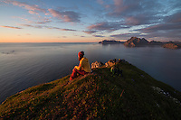 Female hiker waits for sunset over sea from summit of Hornet mountain peak, Flakstadøy, Lofoten Islands, Norway