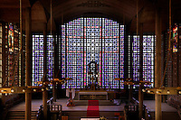 Low angle view of altar and stained glass window with crucifix design in the church of Notre-Dame du Raincy on May 24, 2009 in Le Raincy, Seine Saint Denis, France. Built in 1922-1923 by the architects and brothers Auguste and Gustave Perret, the cathedral was the first one to be built with reinforced concrete. The stained glass was created by Marguerite Hure based on sketches by Maurice Denis. Picture by Manuel Cohen