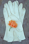 Pair of soft white leather ladies gloves with mother-of-pearl buttons lying on marbled stone with pale orange rose