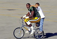 An unidentified Green Bay Packer rides a boy's bike downhill to the Ray Nitschke practice field in 1996.<br /> During Green Bay Packers' training camp, it's tradition for the players to adopt a neighborhood kid and ride that kids bike down the hill for the duration of spring training.