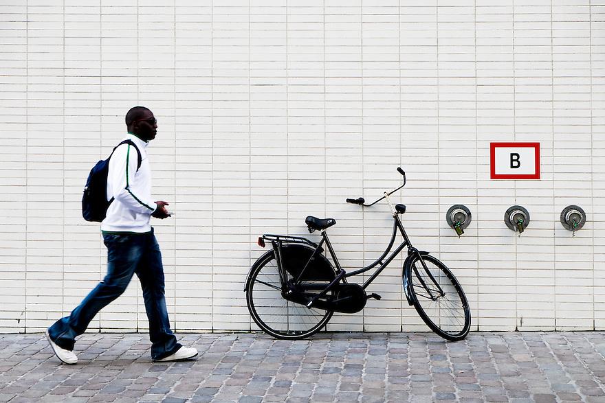 Nederland, Amsterdam, 8 maart  2015<br /> Straatbeeld met donkere man, tegelmuur, fiets en brandkraan. <br /> Foto: (c) Michiel Wijnbergh