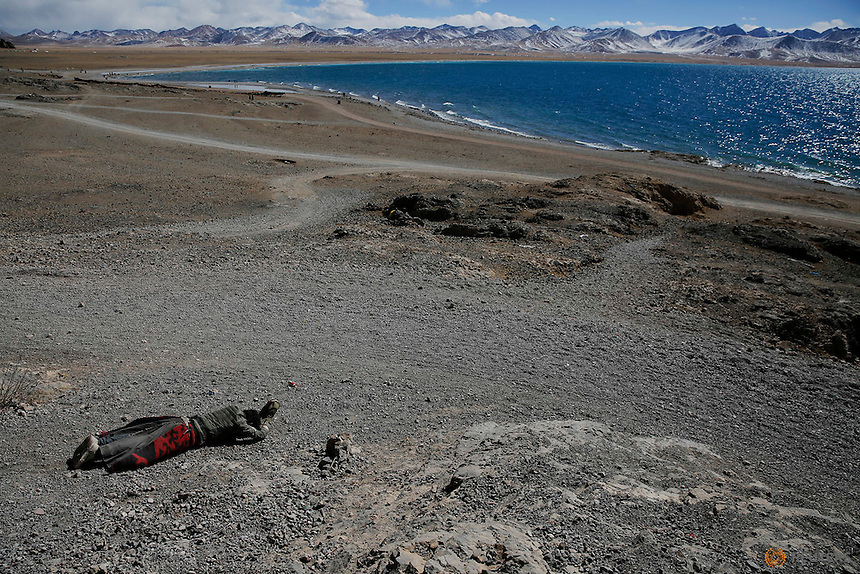 A Tibetan man prostrates himself above Namtso lake in the Tibet Autonomous Region, China November 18, 2015. Located four hours' drive from Lhasa at an altitude of around 4,718m (15, 479 ft) above sea level, Namtso lake is not only the highest saltwater lake in the world but is also considered sacred, attracting throngs of devotees and pilgrims. REUTERS/Damir Sagolj