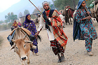 Niko, his wife, and his sister, moving through a village along the Yamuna River.