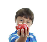A young happy shcool boy hold an apple out for us on white background