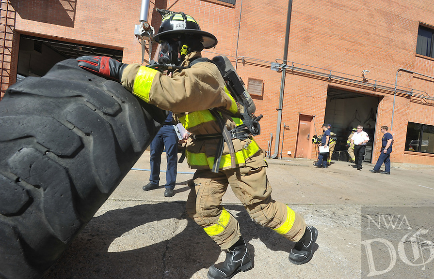 NWA Democrat-Gazette/MICHAEL WOODS &bull; @NWAMICHAELW<br /> James Key, Fayetteville firefighter recruit, flips a tire while wearing his breathing apparatus during a training exercise, March 16, 2016 at Forestation 1 in Fayetteville.  The drill was designed to make the 13 new recruits work with their breathing apparatus until their air tank runs out of oxygen and then learn breathing techniques to maximize the use of the remaining air.