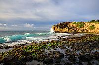 A beautiful light blue-green wave rolls across and into a hidden cove along the Maha'ulepu Heritage Trail, Poipu, Kaua'i.