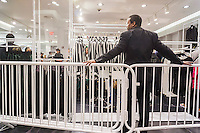 A security guard in the designated Balmain x H&M section of an H&M store in New York on Thursday, November 5, 2015. The collection, designed by the young head of Balmain, Olivier Rousteing, was highly anticipated by fashionistas and drew crowds around the world. In New York H&M instituted a wristband system to time when shoppers could arrive to control crowds. (© Richard B. Levine)