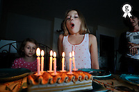 Girl blowing candles out on birthday cake at home (Licence this image exclusively with Getty: http://www.gettyimages.com/detail/84430605 )