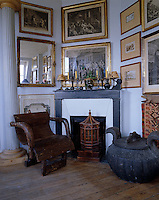 In the living room a large antique jar, an armchair and a wooden birdcage are arranged in front of a fireplace surrounded by framed prints and paintings