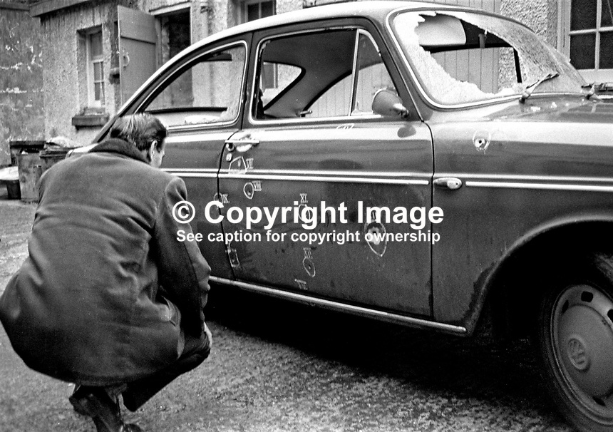 A detective at Dundonald RUC station, N Ireland, examines the vehicle in which Jack Mooney was killed and two colleagues, all Roman Catholics, were travelling when they arrived to start the night shift at the local Rolls-Royce factory. The UDA/UFF gun attack was on New Year's Day 1973, 1st January 1973. Jack Mooney, 31 years, was married with 2 children. His 62 year old father, Hugh Mooney, was among the passengers travelling in the vehicle. For more information see Lost Lives 728. 197301010002a<br /> <br /> Copyright Image from Victor Patterson, 54 Dorchester Park, Belfast, UK, BT9 6RJ<br /> <br /> t1: +44 28 9066 1296 (from Rep of Ireland 048 9066 1296)<br /> t2: +44 28 9002 2446 (from Rep of Ireland 048 9002 2446)<br /> m: +44 7802 353836<br /> <br /> e1: victorpatterson@me.com<br /> e2: victorpatterson@gmail.com<br /> <br /> The use of my copyright images is subject to my Terms &amp; Conditions.<br /> <br /> It is IMPORTANT that you familiarise yourself with them. They are available on my website at www.victorpatterson.com.<br /> <br /> None of my copyright images may be used on a website unless they are visibly watermarked, i.e. &copy; Victor Patterson within the body of the visible image. Metadata denoting my copyright must NOT be deleted. <br /> <br /> Web use (maximum size - 300 kb) is extra at currently recommended NUJ rates.
