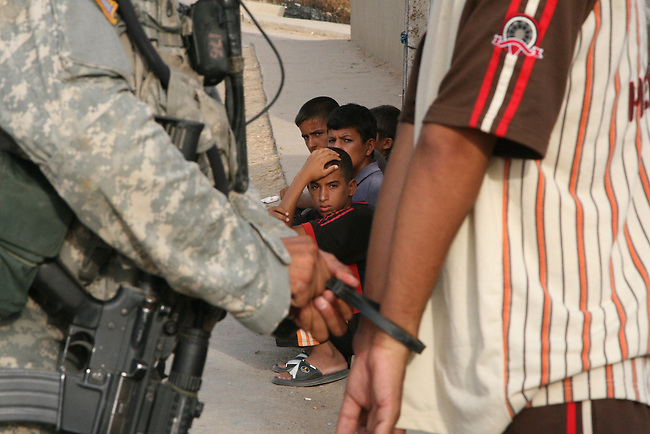 A group of boys looks on as a soldier from Company A, 1st Battalion, 30th Infantry Regiment detains a suspected insurgent in Abuwaitha, Iraq, a village on the Tigris River about 10 miles southeast of Baghdad. Aug. 19, 2007. DREW BROWN/STARS AND STRIPES