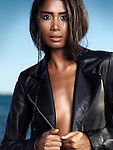 Sexy young woman wearing a black leather jacket over shiny sun tanned body at the beach