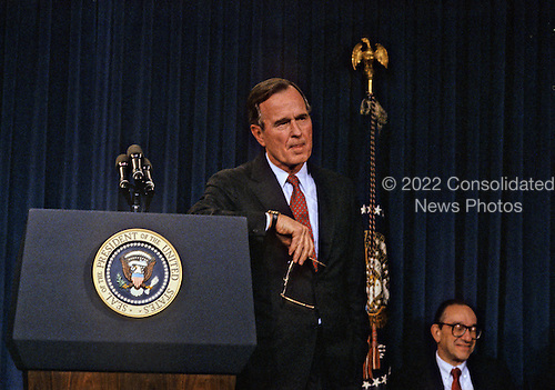 United States President George H.W. Bush announces his savings and loan bailout plan at a press conference at the White House in Washington, D.C. on February 6, 1989.  Alan Greenspan, Chairman of the U.S. Federal Reserve looks on from lower right..Credit: Ron Sachs / CNP