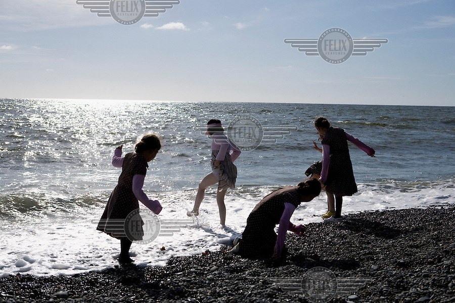 Hasidic girls play by the waters edge on a beach in Aberystwyth.