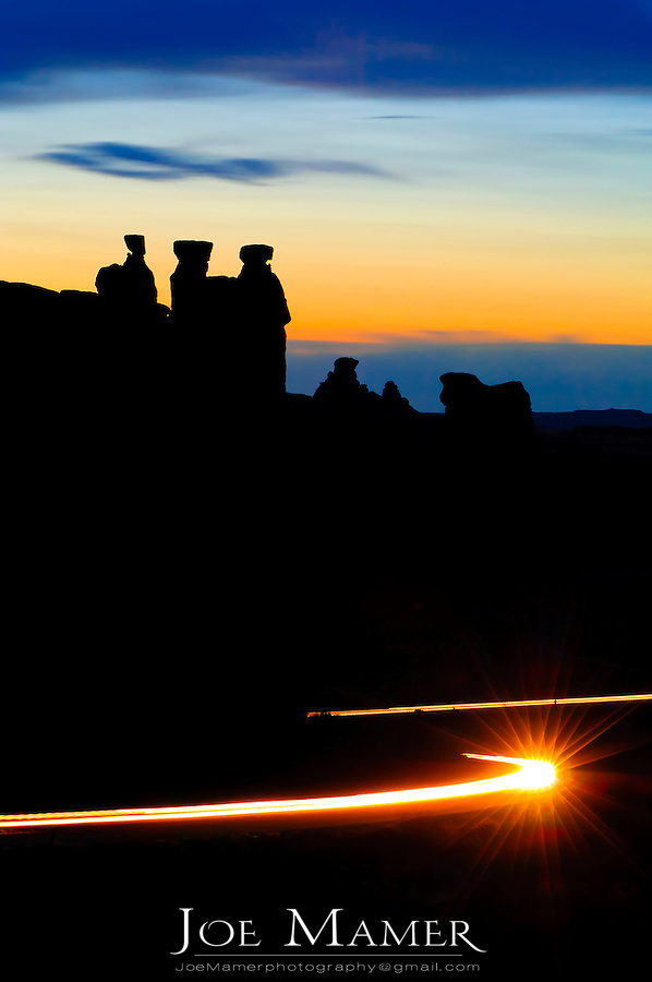 Three gossips at Arches National Park silhouetted against the sunset. Car lights in the foreground trace the path of the road.