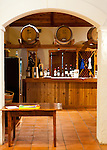 The last pouring station in the Barboursville Vineyards tasting room is visible through an arch from the adjoining gift shop and seating area.  Wines available for pouring at this station are displayed on the bar.  Visitors to the winery move through the tasting room from window to window; each window pours samples of different wines.