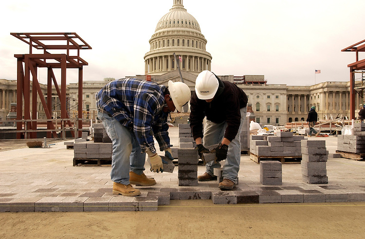 Workers lay paving stone on the site of the Capitol Visitor Center.