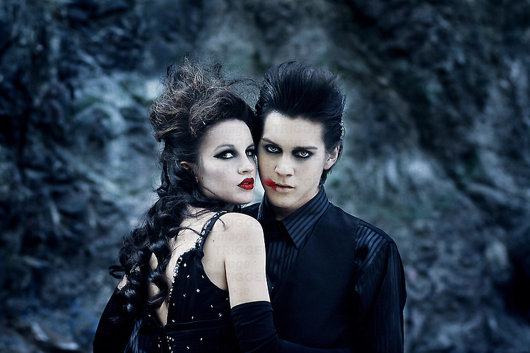 A boy and girl embracing, both of them wearing dark make up.