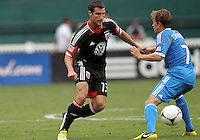 WASHINGTON, D.C. - AUGUST 19, 2012:  Chris Pontius (13) of DC United slips the ball trough the legs of Brian Carroll (7) of the Philadelphia Union during an MLS match at RFK Stadium, in Washington DC, on August 19. The game ended in a 1-1 tie.