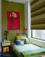 A child's bed placed along the window of this loft apartment has been decorated in a combination of shades of green
