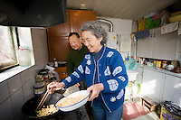 Mr and Mrs Wu cooking beans in their kitchen at home in the Hutongs area, Beijing, China