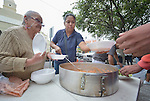 """Maria Natividad Granados (left) and Juani Martinez, both Methodist women in Nuevo Laredo, Mexico, serve food to Cuban immigrants in that city's Plaza Benito Juarez on March 3, 2017. Hundreds of Cubans are stuck in the border city, caught in limbo by the elimination in January of the infamous """"wet foot, dry foot"""" policy of the United States. They are not allowed to enter the U.S. yet don't want to return to Cuba. Many of the city's churches have become temporary shelters for the immigrants, and congregations rotate responsibility for feeding the Cubans, who have slowly been forced to appreciate Mexican cuisine. Such solidarity from ordinary Mexicans is being tested these days, as not only are the Cubans stuck at the border, but the U.S. has stepped up deportations of Mexican nationals, while at the same time detaining many undocumented workers from other nations and simply dumping them on the US-Mexico border. Granados is a member of the El Ebenezer Methodist Church in Nuevo Laredo. Martinez is a member of the Aposento Alto Methodist Church in Nuevo Laredo."""