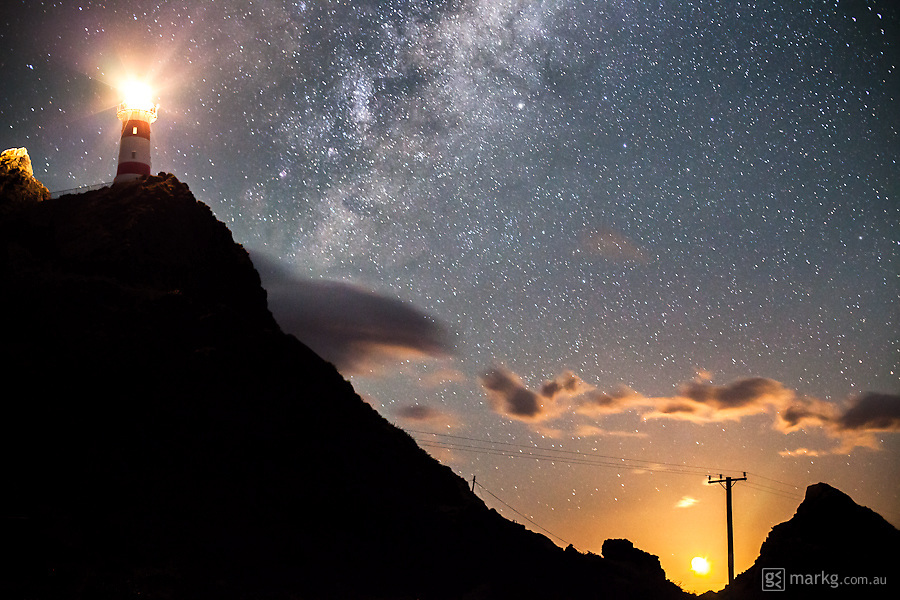 The moon rises above the horizon to the east, as the Milky Way in the sky above shines above the Cape Palliser Lighthouse on the south eastern tip of the North Island of New Zealand