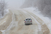 Car driving along  ice covered country road