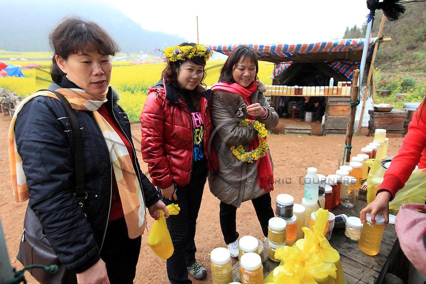 Luoping, Yunnan. Sur l'étal d'un apiculteur, des touristes achètent des kilos de miel. Le miel est un cadeau apprécié des Chinois et certains miels rares se vendent une fortune dans les magasins chics des mégapoles.///Luoping, Yunnan. At a beekeeper's stand, tourists buy kilos of honey. Honey is an appreciated gift for the Chinese and some rare honeys sell for a fortune in the chic shops of the big cities.