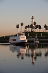 A tour boat coming into Rainbow Harbor, past the Rainbow Harbor Lighthouse on Lighthouse Point, Long Beach, CA