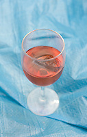A glass of rose wine on a blue background.