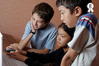 Three children (9-14) using laptop, side view (Licence this image exclusively with Getty: http://www.gettyimages.com/detail/200476761-001 )