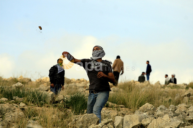 Palestinian demonstrator hurls stones at Israeli soldiers, not seen, during a demonstration against Israel's separation barrier in the West Bank village of Nilin near Ramallah, Friday,January 1, 2010. Photo by Issam Rimawi