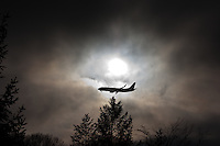 A passenger airliner flies low beneath the cold, cloud-shrouded sun, but above an evergreen tree on a blustery winter day