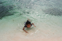 A girl swims in the shallows at Laura Beach, Majuro, Marshall Islands. Most Marshall Islanders are at home in the waters which surround the low atolls which make up the stunningly beautiful country.