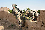 1st Lt. Jim Lazak, a platoon leader with Company B, 2nd Battalion, 508th Parachute Infantry Regiment, helps another soldier over a wall during a patrol in the Arghandab valley near Kandahar, Afghanistan. March 27, 2010. DREW BROWN/STARS AND STRIPES