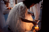 Possessed by the spirit of a dead Brazilian Indian, a medium in the Afro-Brazilian cult of umbanda waves a petition written on a piece of paper over a candle to sanctify the request. Umbanda mediums take on the spirits of the dead to grant favors, offer advice, and counsel the living